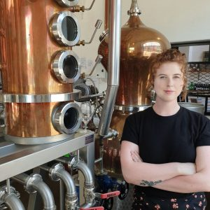 Woman standing next to a copper still